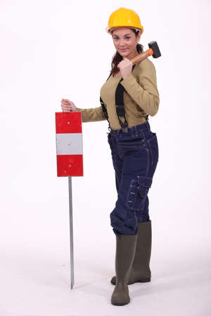 public works: Woman with hammer over hershoulder signaling Stock Photo