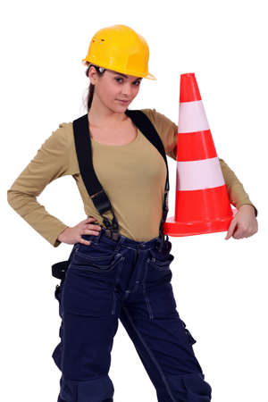 under construction sign: craftswoman holding traffic cone Stock Photo