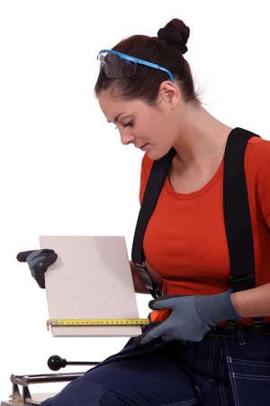 tradeswoman: Tradeswoman measuring a tile Stock Photo