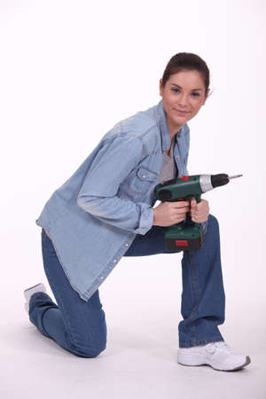 kneel down: portrait of cute brunette holding electric drill