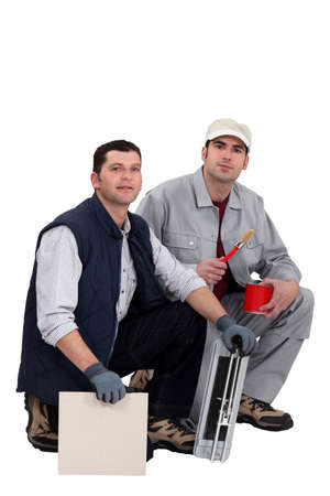 tile cutter: Tile cutter and painter kneeling together Stock Photo