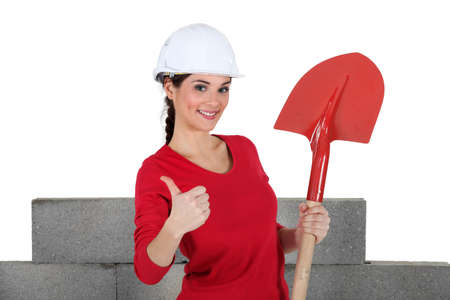 sideway: A female mason with a shovel. Stock Photo