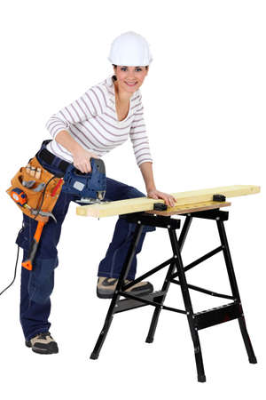 sawyer: Woman sawing wood with electrical saw