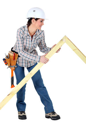 treated board: Female carpenter with wooden frame Stock Photo