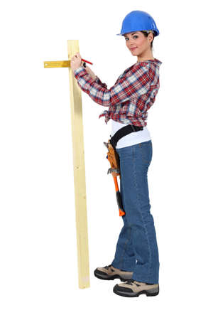 Woman measuring the width of a plank of wood Stock Photo - 15573501