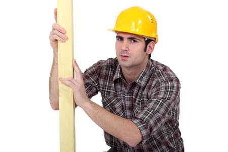trussing: L'uomo l'esame di asse di legno Archivio Fotografico