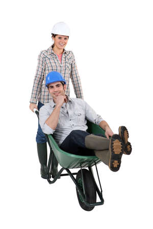 workwoman: Woman pushing a man in a wheelbarrow
