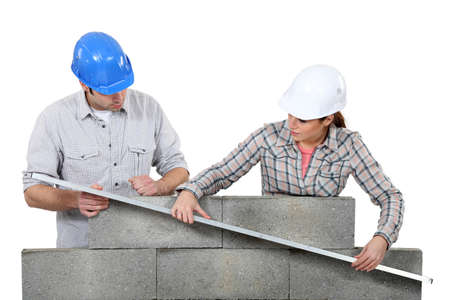 hardworking: Two masons working on a wall. Stock Photo