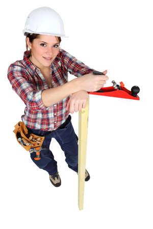Female carpenter with wood plane