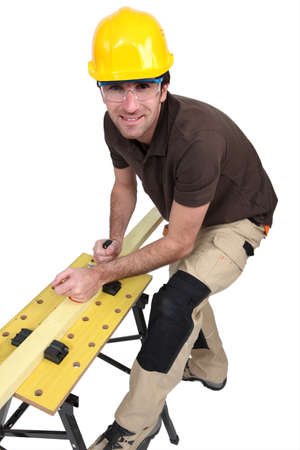 smoothen: Tradesman using a plane to smooth a plank of wood