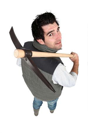 mattock: Man resting pick-axe on shoulder