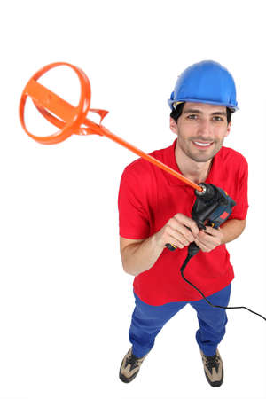 Tradesman holding up a tool for mixing mortar photo