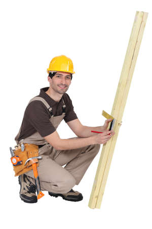 Tradesman taking measurements using a try square photo