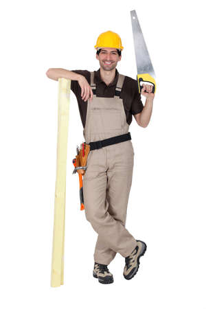 Tradesman holding a saw and a plank of wood Stock Photo - 15573420