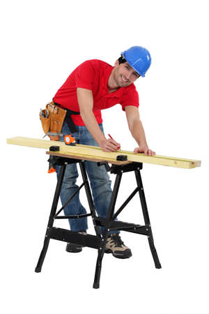 Man marking a measurement on a wooden plank photo