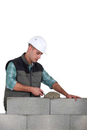 stonemasonry: Man spreading mortar with a trowel Stock Photo