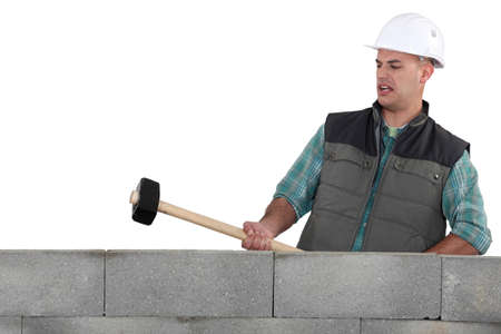 sledge hammer: A mason about to destroy a wall with a sledgehammer.
