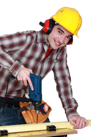 earmuffs: young carpenter all smiles using drill