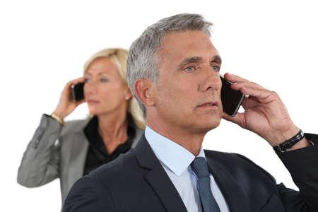 Mature business couple using cellphones Stock Photo - 15574122