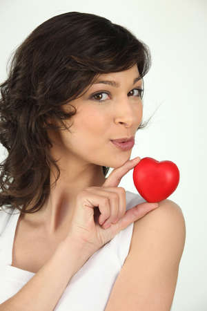 cherishing: a brunette woman and a little red plastic heart