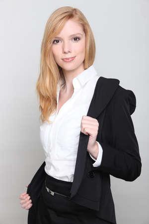 undress: Blond businesswoman removing jacket