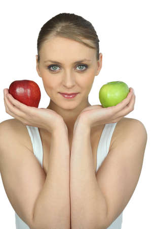 Young woman holding a red and a green apple photo