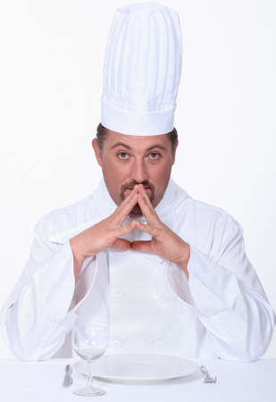 appraising: Chef sitting at a table Stock Photo