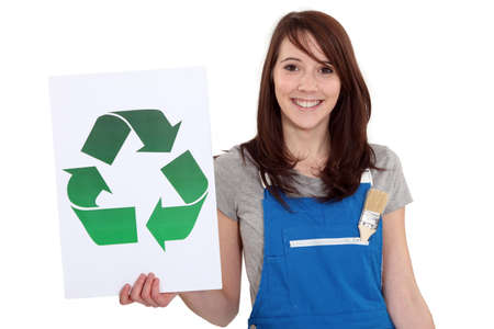 A female manual worker holding a recycle sign. photo