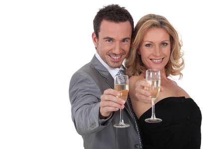 fete: Couple raising champagne glasses