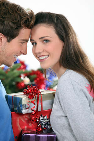 Couple stood by Christmas tree and gifts photo