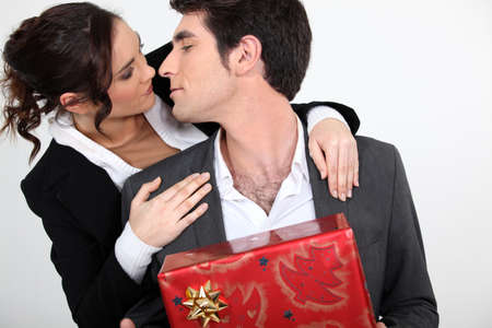 kiss couple: Couple with Christmas present about to kiss