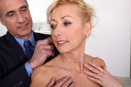 caras emociones: caballero maduro que ofrece su esposa un collar Foto de archivo