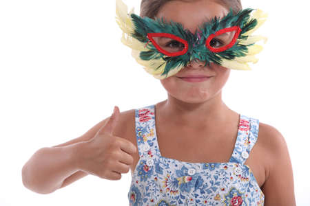 animal masks: Little girl with feather mask Stock Photo