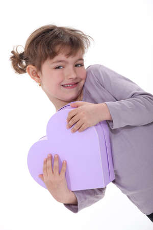Adorable girl hugging a heart-shaped box photo