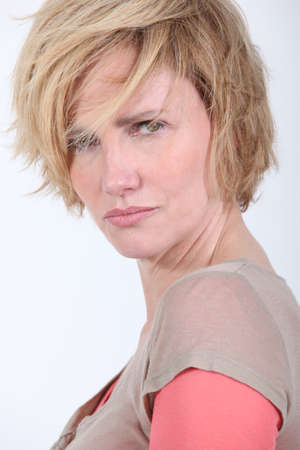 tough woman: 50 years old woman with tousled hair looks anger or in trouble Stock Photo