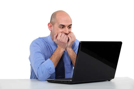 tense: Bald businessman scared by laptop