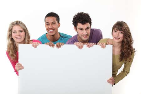 school teens: Los j�venes con un cartel en blanco Foto de archivo