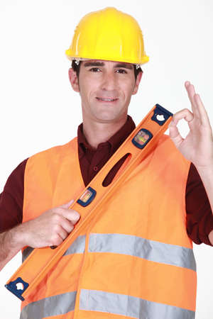 leveler: Man with spirit-level giving the ok sign
