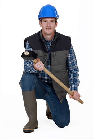 coverall: Man kneeling with sledge-hammer and wellington boots Stock Photo