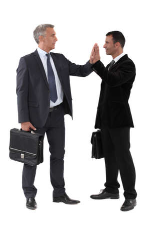 five people: Two businessmen giving each other high-five Stock Photo