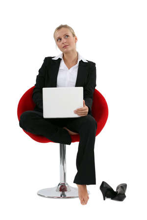 musing: Blond with laptop barefoot Stock Photo