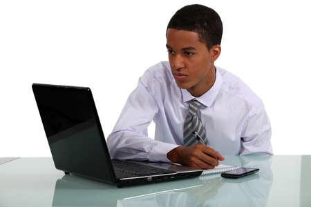 net surfing: Giovane uomo d'affari guardando il suo computer portatile Archivio Fotografico