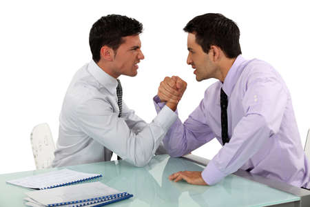 Two businessmen arm wrestling photo