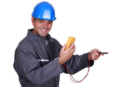 voltmeter: electrician holding a measurement tool and smiling Stock Photo