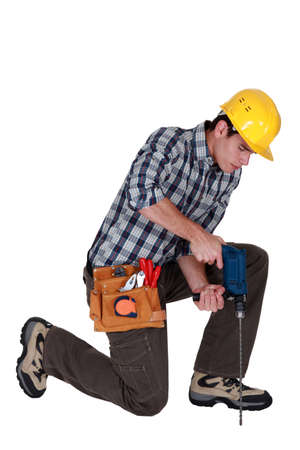 Man kneeling with drill Stock Photo - 15590499