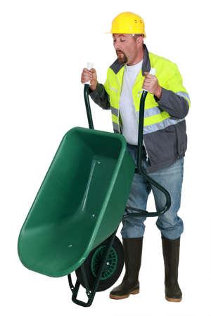 dumping: Man lifting a wheelbarrow