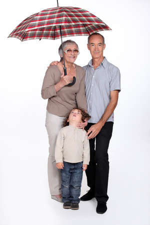 Grandparents and child with an umbrella photo