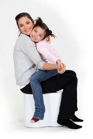 Little girl sat on mother photo