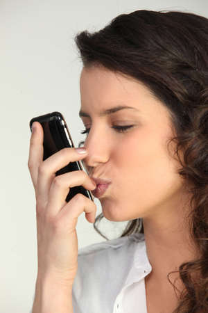 Brunette kissing mobile telephone photo