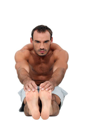 torso only: Fit man touching his toes